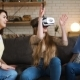Three Young Energetic Girlfriends Laugh and Move Funny Using Together VR Device