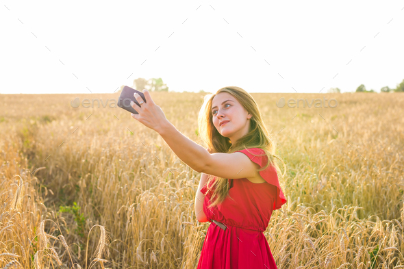 woman taking selfie by smartphone on cereal field - Stock Photo - Images