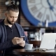 Handsome Bearded Man Dressed in Black T-shirt and Blue Jacket Is Sitting in Cafe