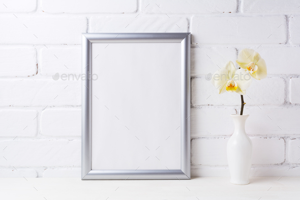 Silver frame mockup with soft yellow orchid in vase - Stock Photo - Images