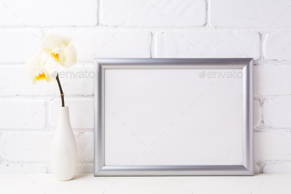 Silver landscape frame mockup with soft yellow orchid in vase - Stock Photo - Images