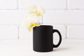 Black coffee mug mockup with soft yellow orchid - PhotoDune Item for Sale