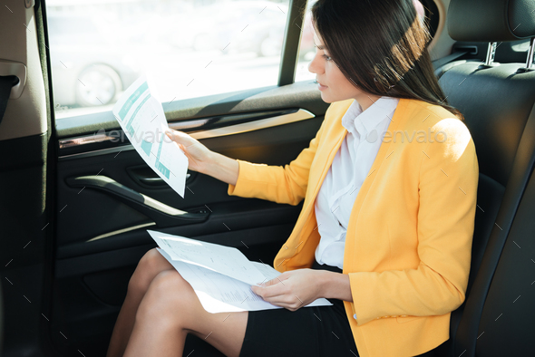 Side view of a concentrated businesss woman analyzing documents - Stock Photo - Images