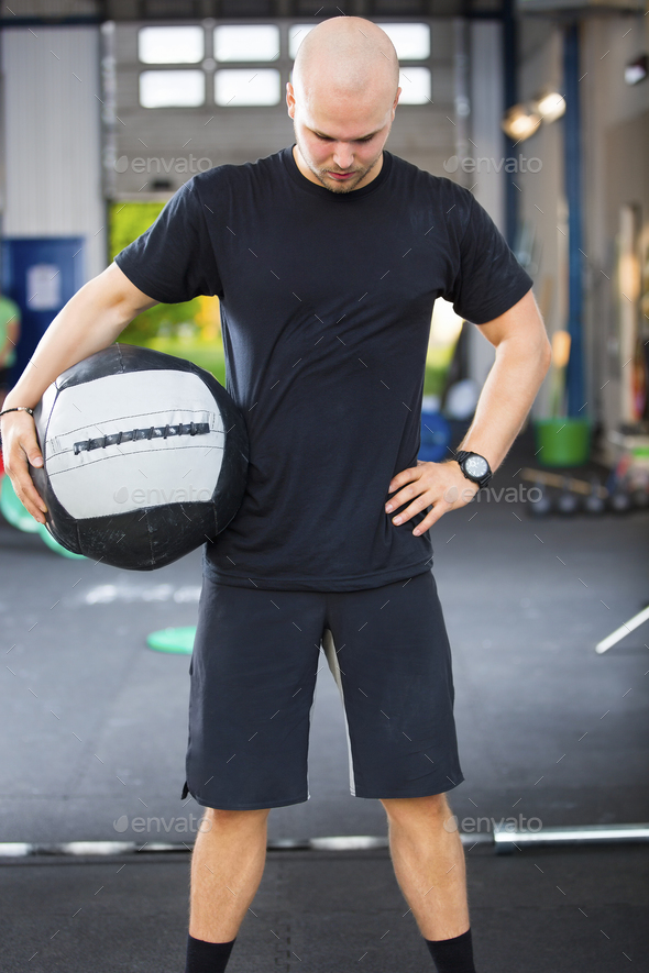 Strong Male Athlete Holding Medicine Ball In Health Club - Stock Photo - Images