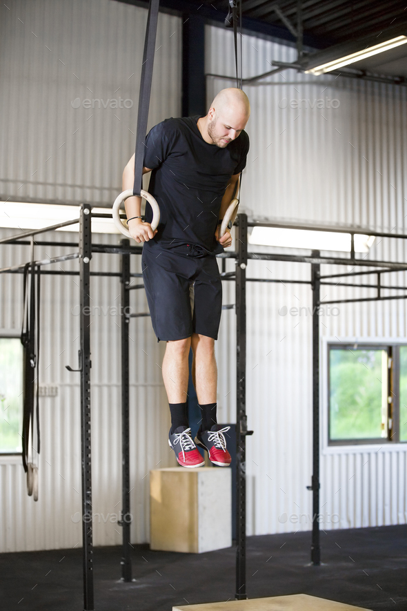 Determined Male Athlete Using Gymnastics Rings In Health Club - Stock Photo - Images