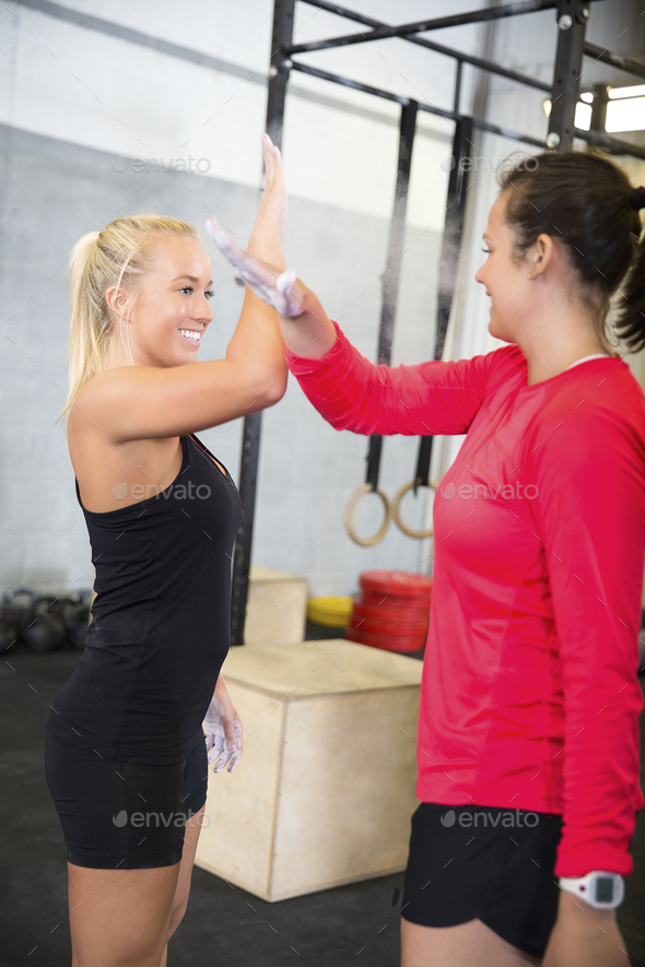 Smiling Female Athletes Giving High Five In Health Club - Stock Photo - Images