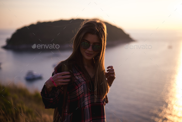 Young stylish hipster girl enjoy sunset on viewpoint. Travel woman with backpack - Stock Photo - Images