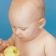 Baby Eats Peeled Apple Holding It in Both Hands - VideoHive Item for Sale