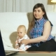 Mother and Blue Eyed Baby Sitting on White Couch Watching Video on Laptop Screen - VideoHive Item for Sale