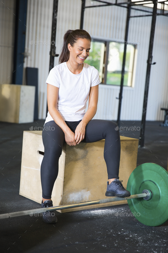 Smiling Athlete Sitting On Box By Barbell In Health Club - Stock Photo - Images