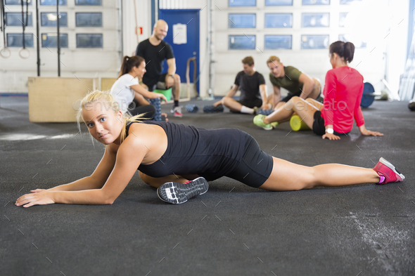 Determined Female Athlete Doing Stretching Exercise At Health Club - Stock Photo - Images