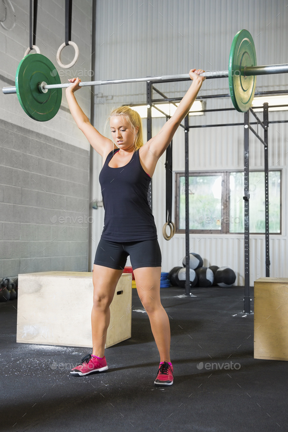 Determined Female Athlete Lifting Weights In Health Club - Stock Photo - Images