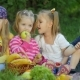 Group of Happy Smiling Children Playing with Vegitables and Fruits Outdoors in Spring Park