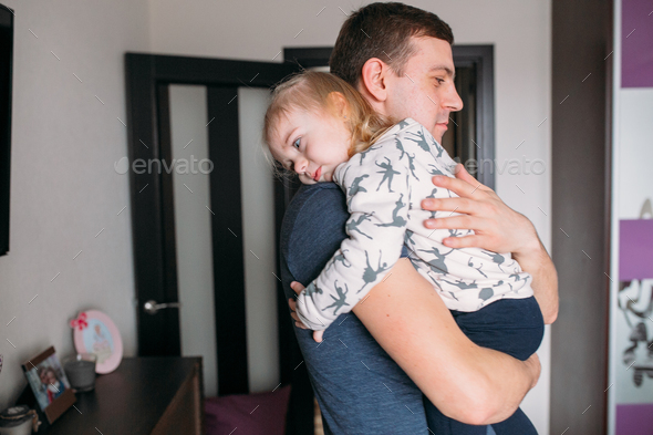 A little girl with a dad in her arms - Stock Photo - Images