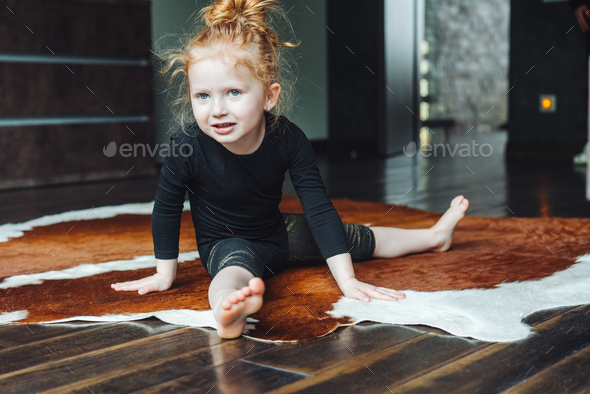 Little girl performs a twine - Stock Photo - Images