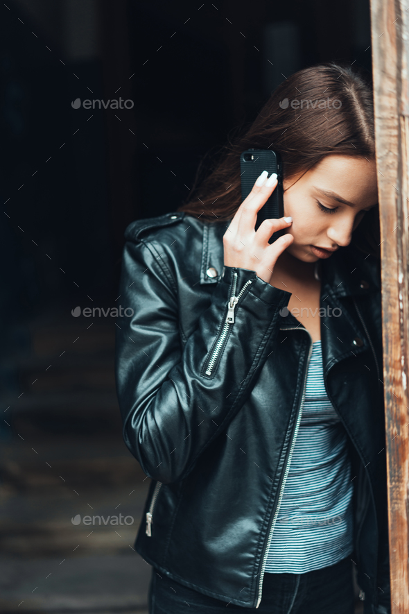 Beautiful girl in black jacket with smartphone - Stock Photo - Images