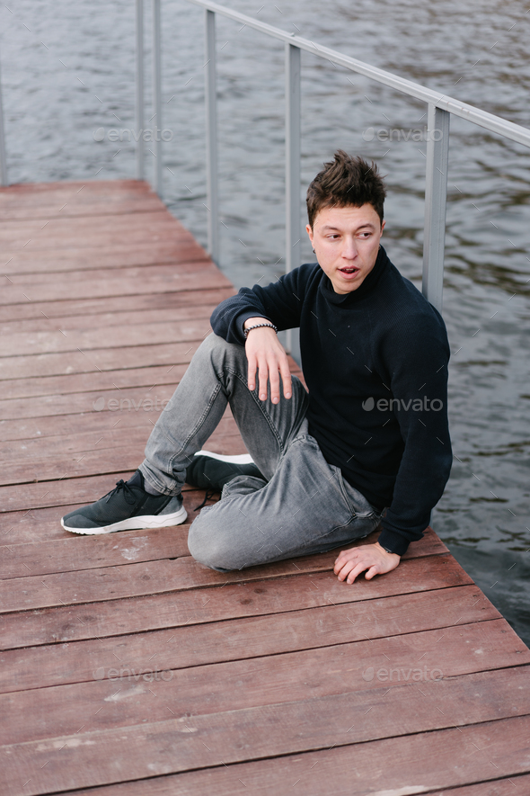 Young man sitting on a wooden pier - Stock Photo - Images