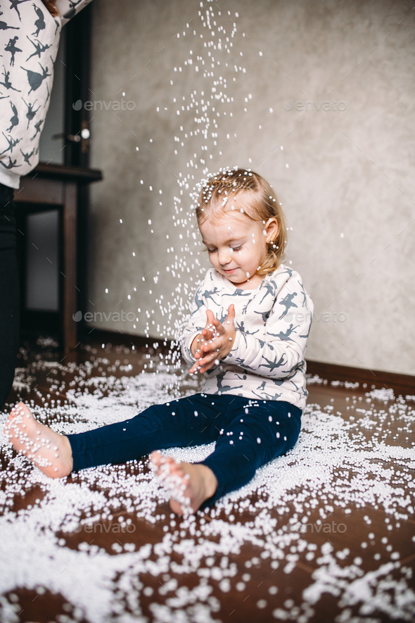 Little girl is playing with foam balls - Stock Photo - Images