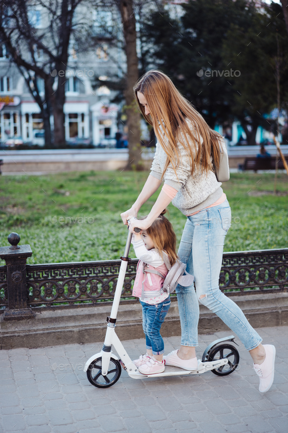 Mom and little daughter on a scooter - Stock Photo - Images