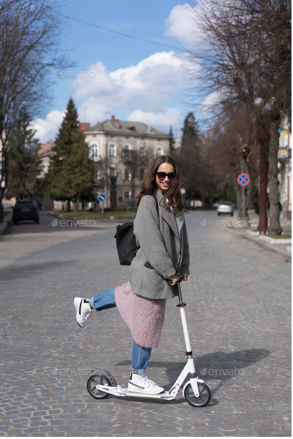 Young girl posing on a scooter - Stock Photo - Images