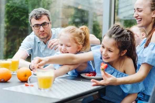 Happy family eating fresh fruit breakfast - Stock Photo - Images