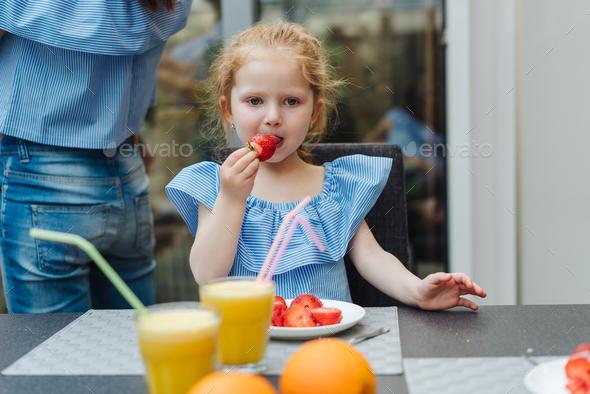 Little girl eating fresh strawberries - Stock Photo - Images