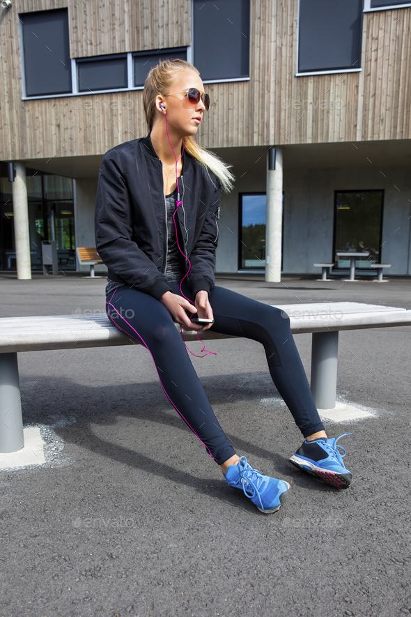 Sporty Woman In Sportswear Listening Music On Bench - Stock Photo - Images