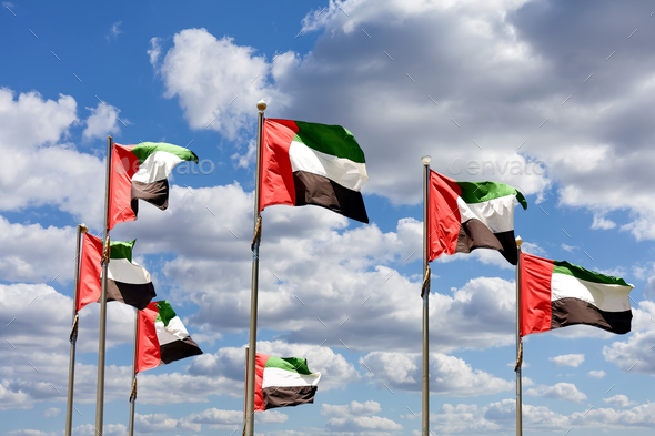 Seven United Arab Emirates flags against blue sky with clouds. - Stock Photo - Images