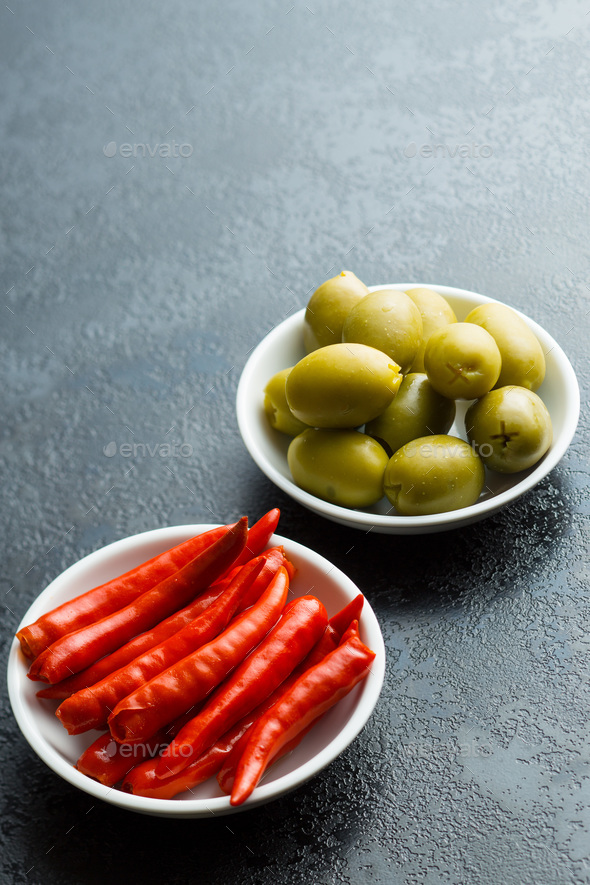 Pickled chili peppers and green olives. - Stock Photo - Images