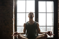 Portrait of a young sportsman meditating in lotus pose while sitting on the windowsill at the gym