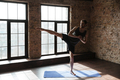 Attractive strong sportsman in gym make yoga exercises.
