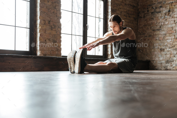 Portrait of a healthy sportsman doing stretching exercises - Stock Photo - Images