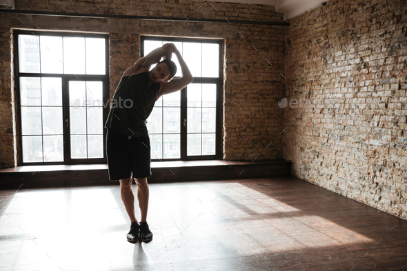 Full length portrait of a young healthy athlete man stretching - Stock Photo - Images