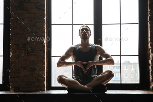 Portrait of a young concentrated sportsman meditating - Stock Photo - Images