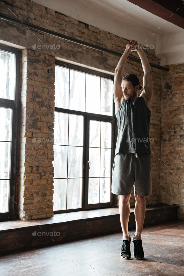 Young healthy athlete man stretching muscles before workout - Stock Photo - Images