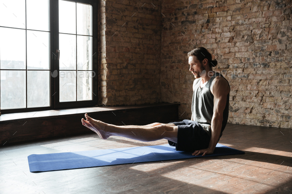 Concentrated strong sportsman in gym make yoga sport exercises - Stock Photo - Images
