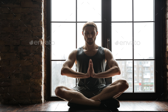 Portrait of a healthy young sportsman meditating in lotus pose - Stock Photo - Images