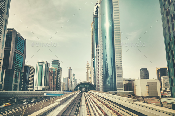 Retro toned photo of Dubai modern downtown seen from metro train - Stock Photo - Images