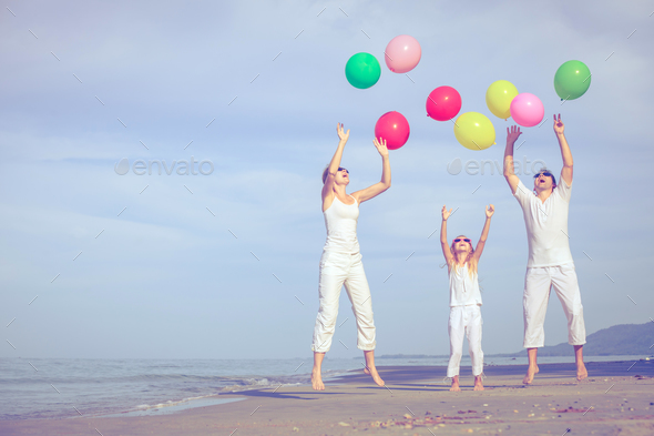 Happy family playing on the beach at the day time. - Stock Photo - Images