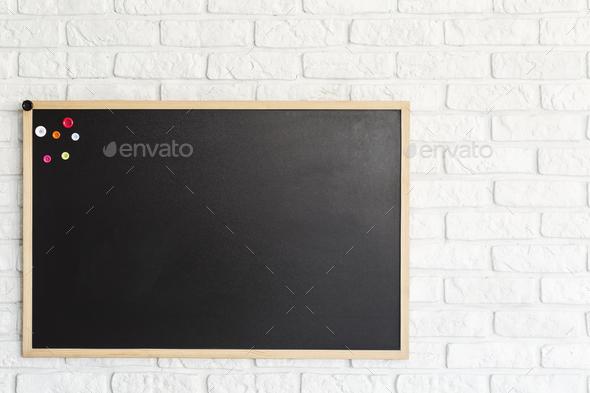 Blackboard hanging on brick wall - Stock Photo - Images