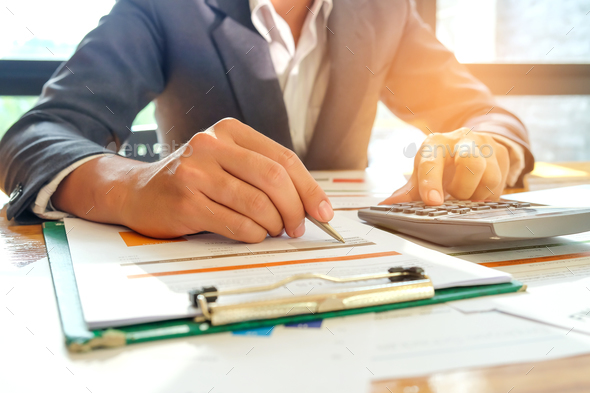 Businessmen are using a calculator and using a pen to analyze da - Stock Photo - Images
