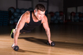Young Man Athlete Doing Pushups With Dumbbells As Part Of Bodybuilding Training.