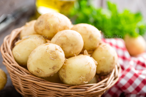 Raw potato in basket on wooden table closeup - Stock Photo - Images