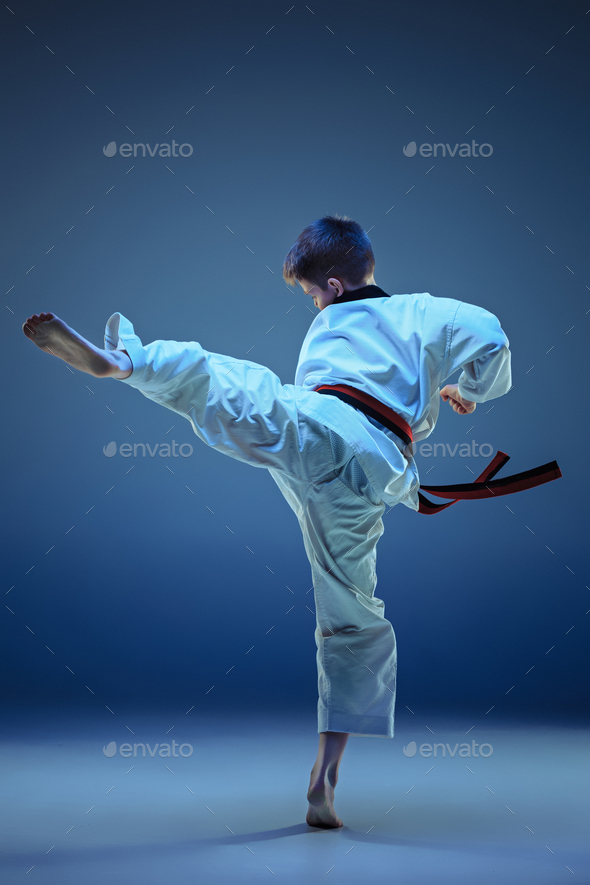 Young boy training karate on blue background - Stock Photo - Images