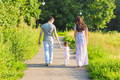 family, parenthood and people concept - happy mother, father and little girl walking in summer park