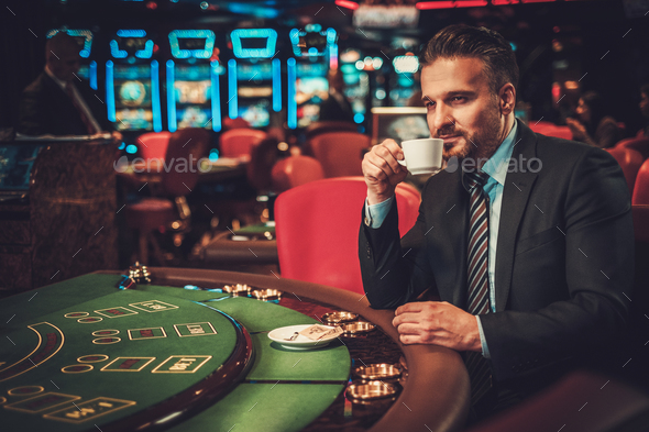 Upper class man behind gambling table in a casino - Stock Photo - Images