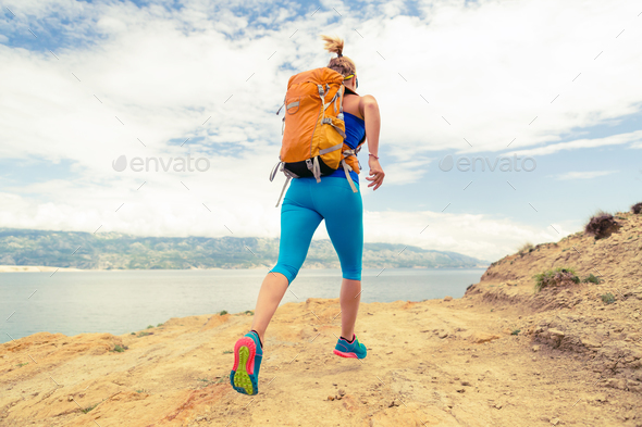 Woman running with backpack on rocky trail at seaside - Stock Photo - Images