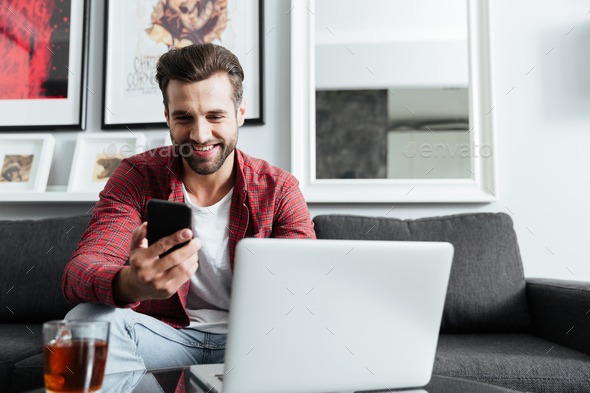 Happy man sitting at home holding telephone - Stock Photo - Images