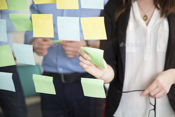 Midsection Of Businesswoman Sticking Note While Standing By Executive - Stock Photo - Images