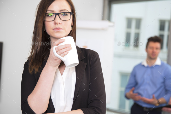 Businesswoman Holding Coffee Mug While Colleague Standing In Bac - Stock Photo - Images